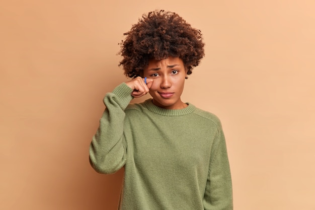 Mulher encaracolada e deprimida e decepcionada enxuga as lágrimas carrinhos estressados com uma expressão sombria vestida em poses de vestido laranja da moda contra a parede azul