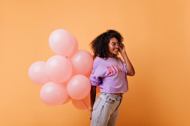 Mulher encaracolada elegante em copos segurando balões de hélio rosa e rindo. feliz aniversariante africano isolada em laranja.