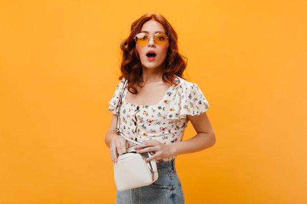 Mulher encaracolada em óculos de sol confusamente olha para a câmera e segura uma pequena bolsa branca.