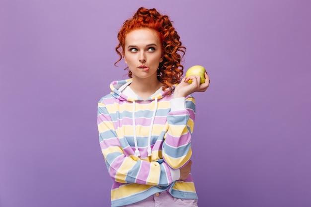 Mulher encaracolada em um moletom multicolorido morde o lábio e segura uma maçã na parede isolada