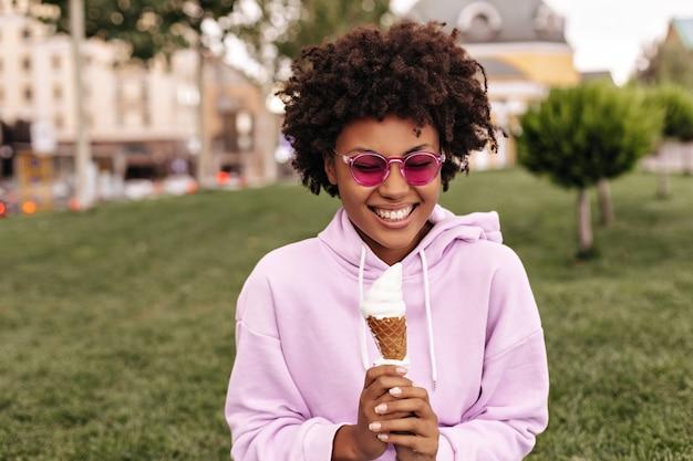 Mulher encaracolada feliz e animada com óculos escuros fúcsia e capuz rosa, sorrindo sinceramente e segurando um sorvete