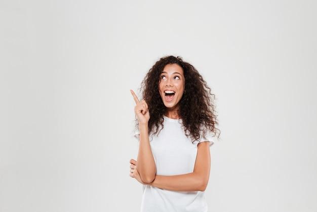 Mulher encaracolada feliz tendo idéia e mostrando o dedo indicador enquanto olhando para cima sobre fundo cinza