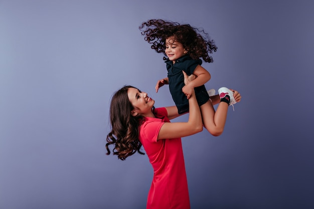 Mulher encaracolada inspirada brincando com a irmã mais nova. maravilhosa jovem mãe aproveitando o tempo de lazer com a filha.