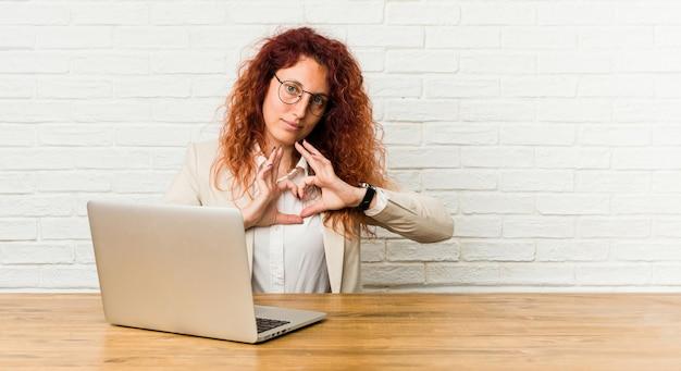 Mulher encaracolada jovem ruiva trabalhando com seu laptop, sorrindo e mostrando uma forma de coração com as mãos.