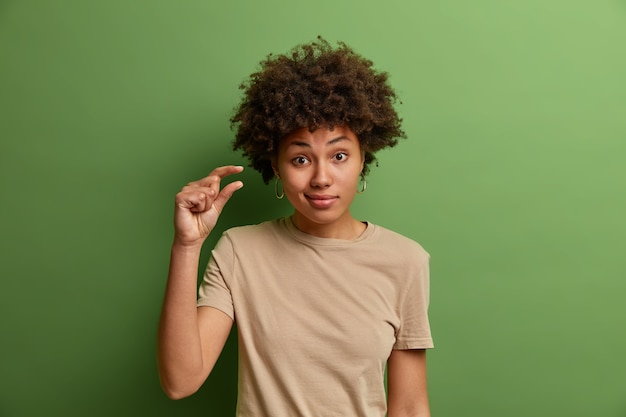 Mulher encaracolada não impressionada mostra um pouco mais ou um pouco de gesto, demonstra poucos centímetros ou sentímetro, sinal de pequena quantidade ou escala baixa, vestido com roupas casuais, isolado na parede verde
