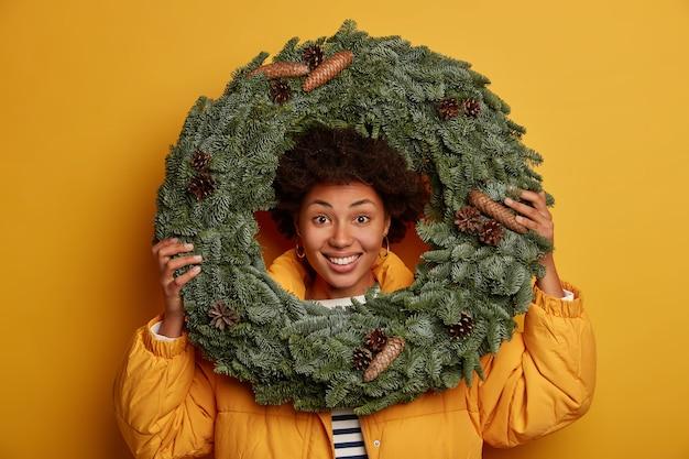 Mulher encaracolada otimista olha através da guirlanda de natal artesanal, estando de bom humor, usa o casaco acolchoado, fica contra um fundo amarelo.