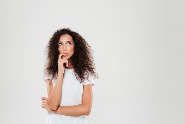 Mulher encaracolada pensativa com o dedo perto da boca, olhando para longe
