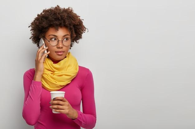 Mulher encaracolada pensativa fala ao telefone pelo celular, bebe café, gosta de conversar, usa óculos, gola alta rosa com lenço amarelo, posa contra um fundo branco