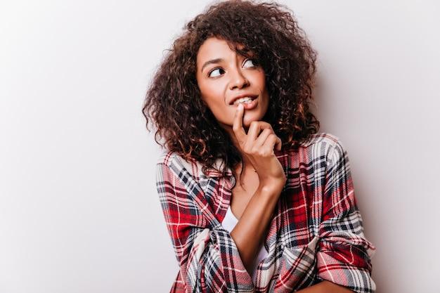 Mulher encaracolada pensativa olhando ao redor e tocando seu queixo. modelo feminino africano de camisa quadriculada isolada na luz.