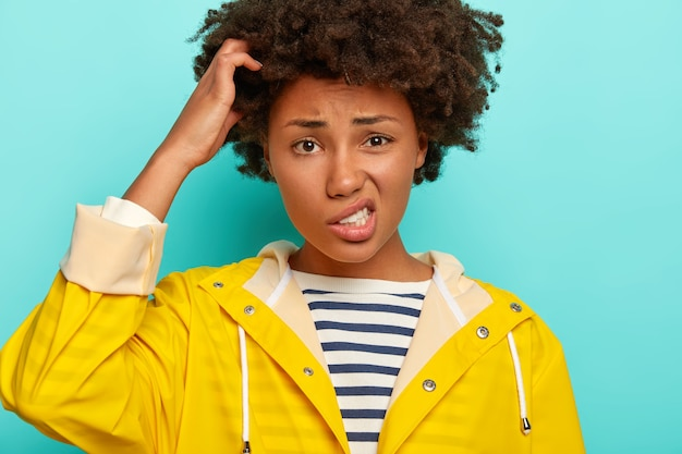 Mulher encaracolada perplexa coça a cabeça, sorri afetadamente e olha confusa para a câmera, enfrenta uma situação problemática, usa capa de chuva impermeável amarela, isolada sobre fundo azul