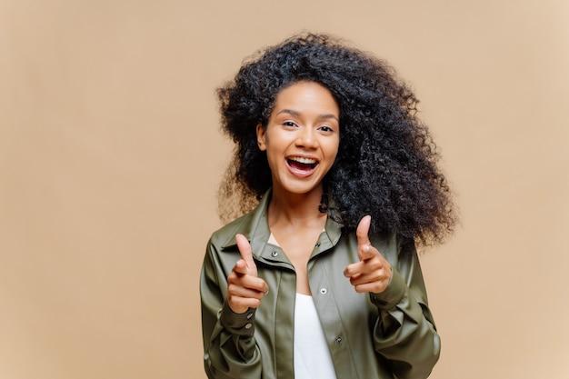 Mulher encaracolada positiva com cabelos luminosos e roupas casuais