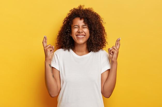 Mulher encaracolada positiva cruzando os dedos