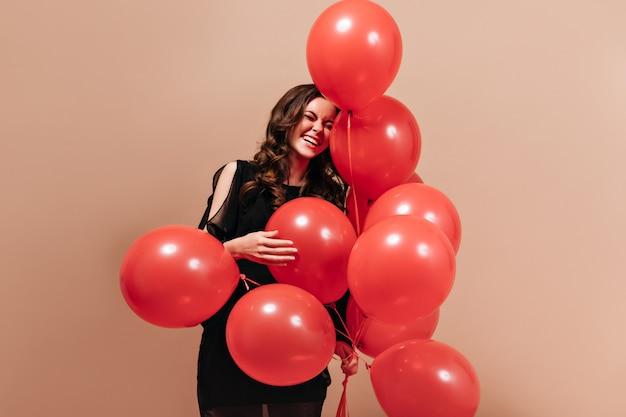 Mulher encaracolada positiva em roupa preta ri e posa com balões vermelhos em fundo isolado.