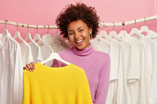 Mulher encaracolada positiva segura o suéter amarelo nos cabides, experimenta roupas novas, seleciona roupas para ocasiões casuais, tem uma expressão feliz
