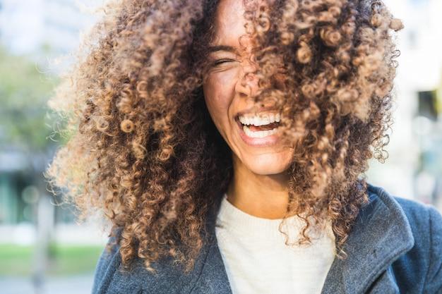 Mulher encaracolada rindo e balançando a cabeça
