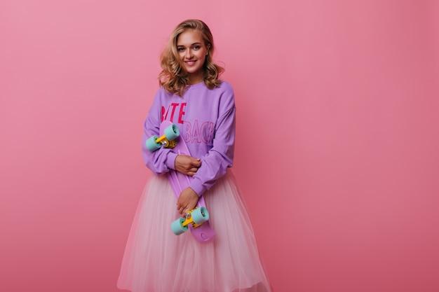 Mulher encaracolada satisfeita segurando longboard rosa e sorrindo. modelo feminino exuberante em saia exuberante, posando em pastel com emoções sinceras.