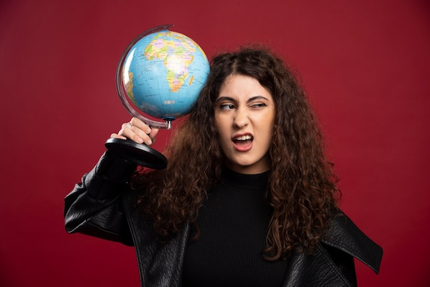 Mulher encaracolada segurando o globo.