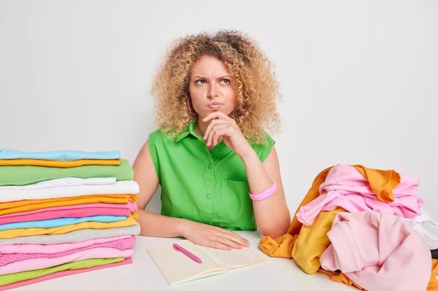 Mulher encaracolada séria e atenciosa coleta roupas para doação faz anotações no diário cercada por roupas dobradas e desdobradas