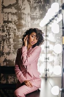 Mulher encaracolada sonhadora em um terno rosa sentada perto do espelho