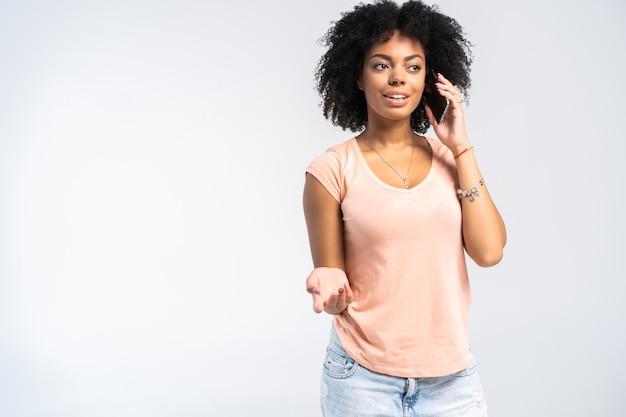 Mulher encaracolada sorridente com smartphone nas mãos, olhando para a câmera sobre o branco.