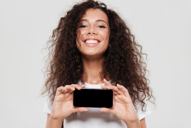 Mulher encaracolada sorridente, mostrando a tela do smartphone em branco