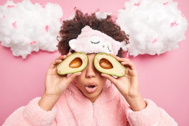 Mulher encaracolada surpreendida cobre os olhos com metades de abacate usa para cuidados cosméticos naturais com a pele mantém a boca aberta de maravilha usa máscara e pijama