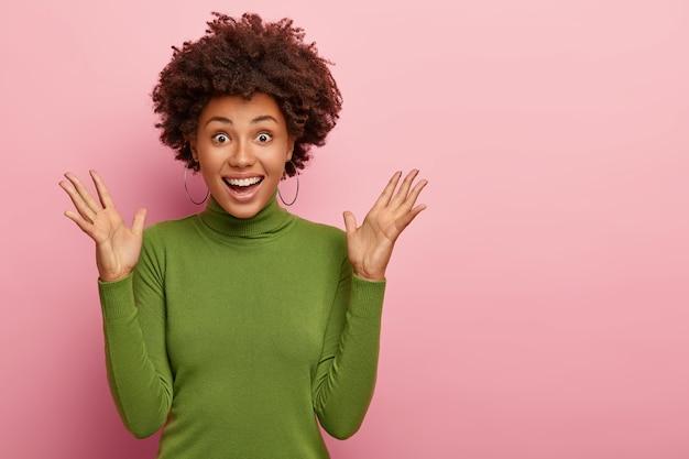 Mulher encaracolada surpresa e emotiva levanta as mãos de alegria, junta as mãos, aplaude e se sente energizada, usa gola olímpica verde, brincos de prata, sorri amplamente, isolada sobre parede rosa, recebe boas notícias positivas