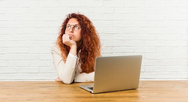 Mulher encaracolado do ruivo novo que trabalha com seu portátil que olha lateralmente com expressão duvidosa e cética.