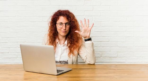 Mulher encaracolado do ruivo novo que trabalha com seu portátil que sorri mostrando alegre número cinco com dedos.