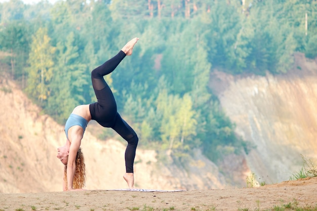 Mulher encaracolado ruiva atraente ou modelo praticando ioga ao ar livre