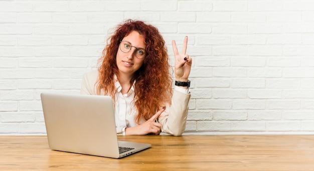 Mulher encaracolado ruiva jovem trabalhando com seu laptop, mostrando o número dois com os dedos.
