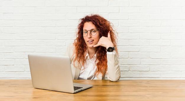 Mulher encaracolado ruiva jovem trabalhando com seu laptop, mostrando um gesto de chamada de telefone móvel com os dedos.