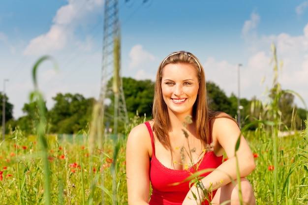 Mulher encolhida no prado de campo