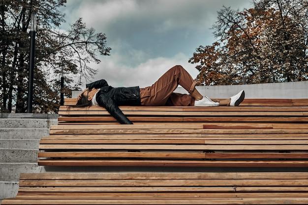 Mulher encontra-se em um banco de madeira. sessão de fotos na cidade.