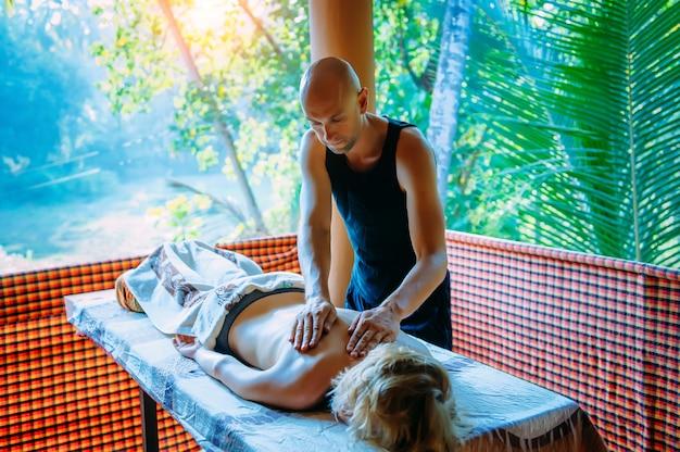 Mulher encontra-se na mesa de massagem na varanda com vista para vegetação de palma durante a sessão de massagem corporal de bem-estar