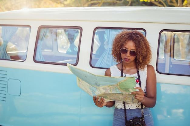 Mulher encostada na caravana e olhando para o mapa