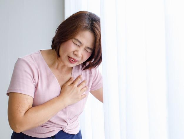 Mulher encostada na parede com dor, sofre e rosto distorcido e usa a mão para segurar no peito de doença cardíaca. conceito de infarto do miocárdio com elevação do segmento st.