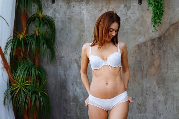 Mulher encostada na parede de concreto com plantas tropicais verdes ao redor e posando de sutiã e calça branca