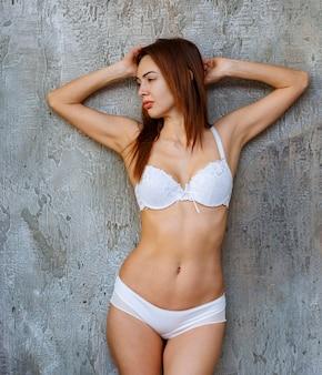 Mulher encostada na parede de concreto e posando de sutiã e calça branca.