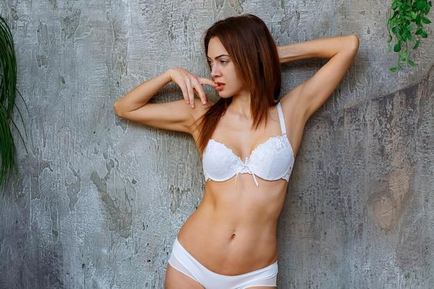 Mulher encostada na parede de concreto e posando de sutiã e calça brancos enquanto colocava o dedo na boca.