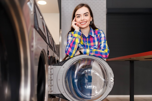 Mulher encostada na porta da máquina de lavar roupa na lavanderia self-service