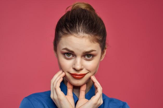 Mulher enérgica com maquiagem brilhante e uma camisa azul sobre um fundo rosa gesticula com as mãos.