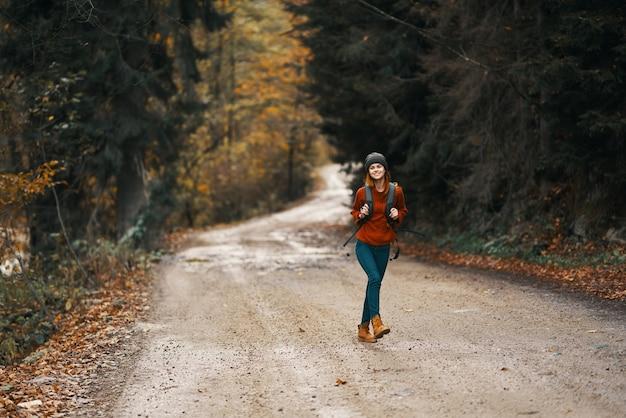 Mulher enérgica correndo ao longo da estrada com uma mochila na floresta de outono
