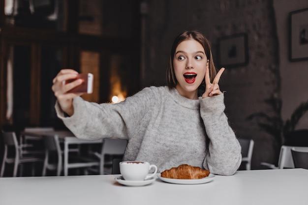 Mulher enérgica de suéter cinza e batom vermelho faz selfie. retrato de menina mostrando sinal de paz no café com croissant na mesa.