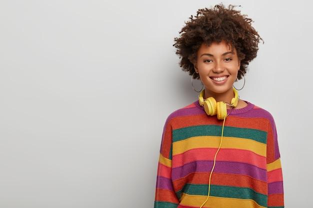 Mulher enérgica e entusiasmada com cabelo crespo encaracolado, ouve música no fone de ouvido, sorri amplamente, estando em alto astral, fica de pé contra um fundo branco