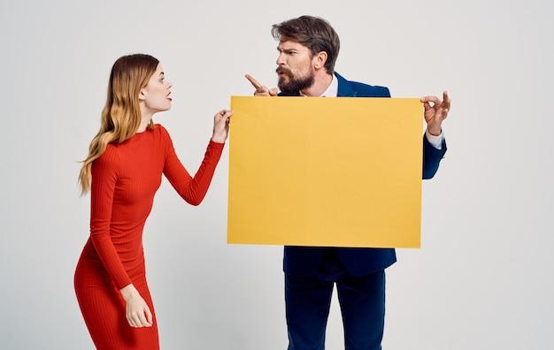 Mulher enérgica pega o cartaz de maquete das mãos de um modelo de publicidade de homem.