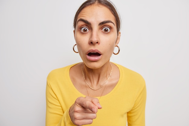 Mulher engasga com a maravilha apontando diretamente para a câmera com o dedo indicador segurando a respiração de espanto usa um macacão amarelo casual em branco percebe quem é o culpado
