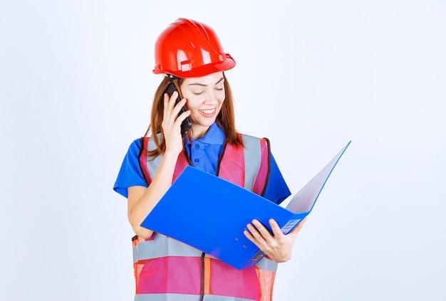 Mulher engenheira com capacete vermelho, falando ao telefone.