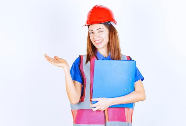 Mulher engenheira de capacete vermelho segurando uma pasta de projeto azul e apresentando alguém ou algo.