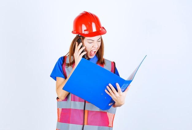 Mulher engenheira de uniforme e capacete vermelho, segurando uma pasta azul e gritando ao telefone.